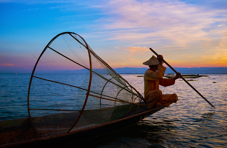 The fisherman floats in cano boat, sitting on its edge with a paddle and dressed in ethnic attire with conical hat, Intha, Inle Lake, Myanmar.