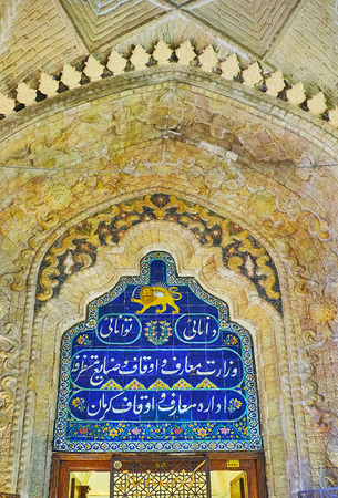 KERMAN, IRAN - OCTOBER 15, 2017: The arch above the door of Hayati Museum is decorated with Lion and Sun (one of main emblems of Persia) and Persian calligraphy on blue tiles, on October 15 in Kerman. Editöryel
