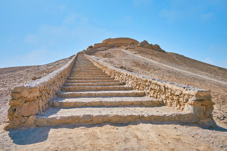 The long stone staircase leads to the hilltop, ending with ancient Zoroastrian burial structure - Tower of Silence (Dakhma), Yazd, Iran.