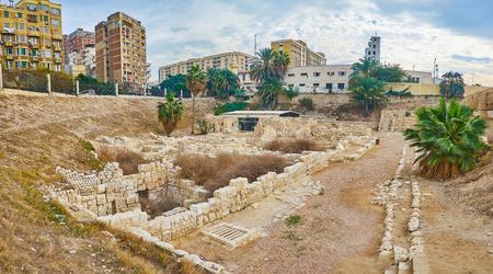 The stone ruins of the Roman village with Villa of Birds on background, Kom Ad Dikka, Alexandria, Egypt.