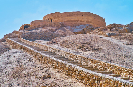The narrow curved stone staircase leads to the top of the rock with preserved Tower of Silence - Zoroastrian place for burial rituals, Yazd, Iran.