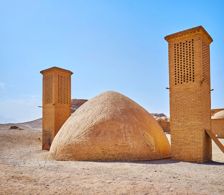The brick dome with two windcatchers is ancient ice chamber, named yakhchal and located in archaeological site of Towers of Silence, Yazd, Iran.