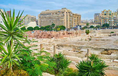 The antique ruins of Roman Auditorium and bathhouse (thermae) of Kom Ad Dikka archaeological site are neighboring with modern city quarters, Alexandria, Egypt.