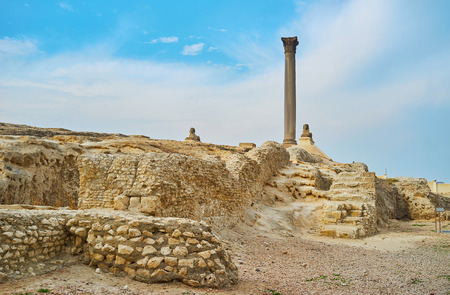 The giant stone monolithic Pompey's Pillar located among the ruins of ancient Serapeum - the Greek Temple, dedicated to Serapis, Alexandria, Egypt.