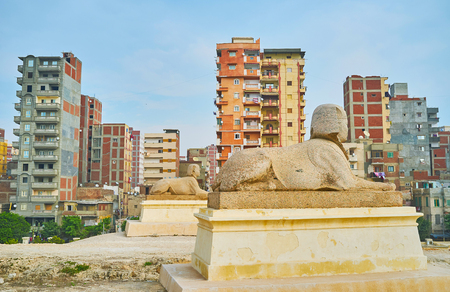 The urban scene with two statues of sphinxes on the foreground, Amoud Al Sawari archaeological site, Alexandria, Egypt.