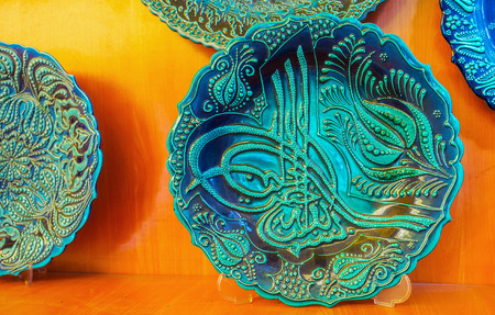 ANTALYA, TURKEY - MAY 11, 2018: The carved souvenir plate in blue gamma, decorated with Ottoman tughra - calligraphic monogram of Sultan, on May 11 in Antalya. Editorial