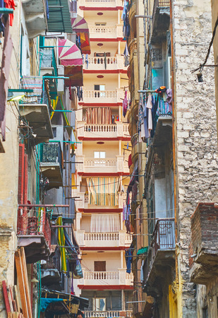 The narrow street in El Labban neighborhood with a view on the modern high-rise through the shabby balconies of old buildings, Alexandria, Egypt