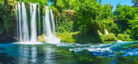 The misty (milky) effect waters of Upper Duden Waterfall with dark blue surface of Duden river and lush park in gorge around the falls, Antalya, Turkey.