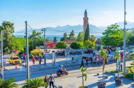 ANTALYA, TURKEY - MAY 11, 2017: The busy Republic street with horse carriages, tall minaret of Alaaddin mosque (Yivliminare) and foggy Taurus mountains on background, on May 11 in Antalya.
