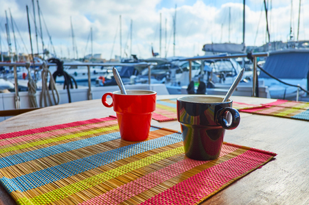 The morning cup of tea with a view on Valletta marina with numerous sailing yachts on background, Malta.