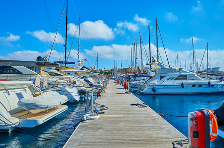 The walk along the wooden shipyard with a view on luxury sailing yachts, moored on both sides, Valletta, Malta.