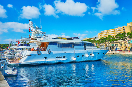 VALLETTA, MALTA - JUNE 17, 2018: The scenic white yacht is moored in Marina of Valletta with a view on Ta'Xbiex promenade on background, on June 17 in Valletta.