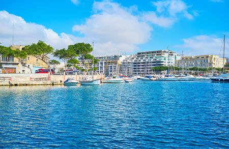 The coast of Ta'Xbiex with row of modern hotels, green pines along the promenade and yachts at marina, Malta. Archivio Fotografico