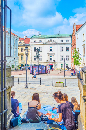 KRAKOW, POLAND - JUNE 11, 2018: The students of Art Academy create the sketches and paintings of architectural forms, sitting in shade of the stone fence in Godzka street, on June 11 in Krakow. Editorial