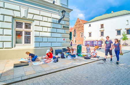 KRAKOW, POLAND - JUNE 11, 2018: The young artists create paintings of beautiful medieval architecture in old town, on June 11 in Krakow. Editorial