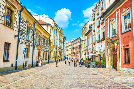 KRAKOW, POLAND - JUNE 21, 2018: Walk along the narrow crowded Kanonicza street - one of the oldest city locations with preserved medieval palaces, mansions and museums, on June 21 in Krakow. 報道画像