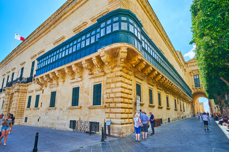 VALLETTA, MALTA - JUNE 17, 2018: The Old Theatre street stretches along the side wall of Grandmaster's Palace  with a view on scenic wooden balcony and Palace arch, on June 17 in Valletta. Sajtókép