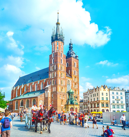 KRAKOW, POLAND - JUNE 11, 2018: The Main Market Square is the center of tourist city life with slow riding horse carriages and street dancers, on June 11 in Krakow.2