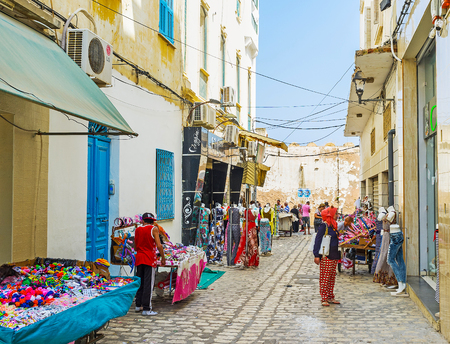 SOUSSE, TUNISIA - AUGUST 28, 2015: The narrow street of garment market next to the ramparts of old Medina, on August 28 in Sousse. Редакционное