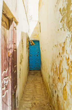The narrow backstreet with shattered plaster on the high walls and old wooden doors, Medina, Sousse, Tunisia. Stock Photo