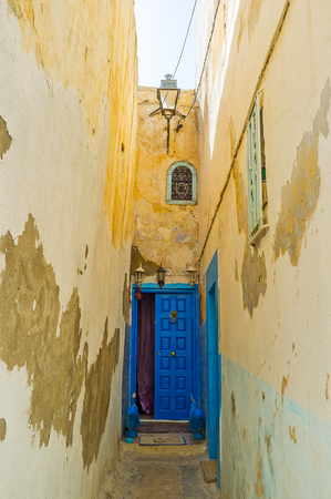 Chaotic medieval housing of Medina is rich in curved backstreets and narrow lanes with high walls and small wooden doors, Medina, Sousse, Tunisia.