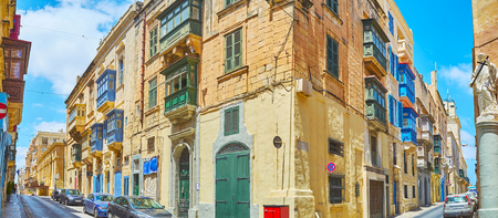 Panoramic view of the corner of St Paul's and Archbishop streets with old buildings, colorful Maltese balconies and the corner statue of St Luigi with Cross, Valletta, Malta.