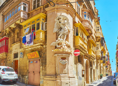 VALLETTA, MALTA - JUNE 17, 2018: The corner statue, also named the niche of St Michael, fighting the Satan, decorates the old edifice in of Archbishop's and St Ursula's streets intersection, on June 17 in Valletta. 에디토리얼