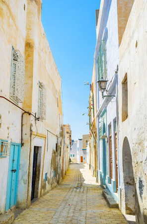 The daily walk in old Medina - one of the main fine preserved city landmarks, the tilted walls of medieval residential houses make the street curved, Kairouan, Tunisia.
