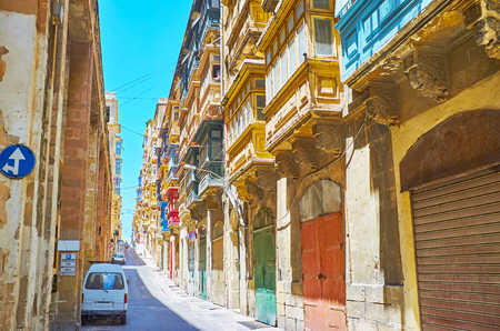 Walking the hilly St Dominic street with a view on historical edifices with hundreds of Maltese balconies, painted in bright colors, Valletta, Malta. Фото со стока