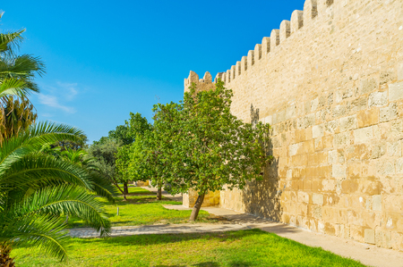 The old Medina of Sousse is surrounded by massive rampart with scenic green garden next to it, Tunisia.