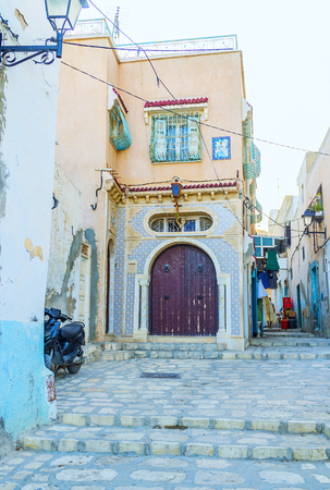 The mansion with arched door and a wall, decorated with tiled patterns in Sousse Medina, Tunisia. Stock Photo
