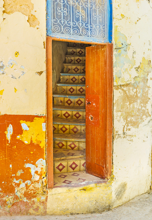 The old house with shattered paint on walls with a view on the tiled staircase through the open door, Sfax, Tunisia.