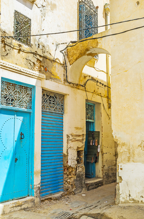The old narrow backstreet with bright blue doors of workshops and small shops, Sfax, Tunisia.