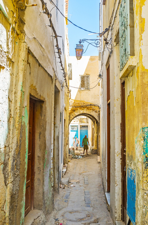 SFAX, TUNISIA - SEPTEMBER 3, 2015: Walking the old narrow streets of Medina, lined with shabby building sof local workshops and living houses, on September 3 in Sfax.