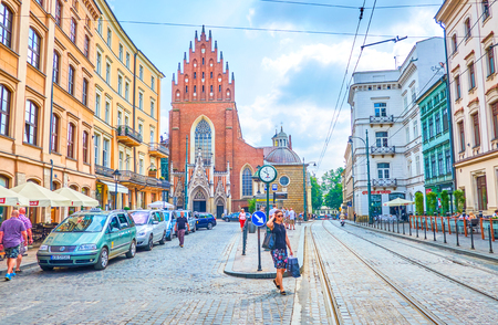 KRAKOW, POLAND - JUNE 11, 2018: The urban scene of Dominican Sqaure with huge medieval Holy Trinity Basilica on background, on June 11 in Krakow.