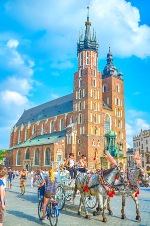 KRAKOW, POLAND - JUNE 11, 2018: Riding on horse-drawn carriages in the crowded city center is a special experience during visiting Krakow, on June 11 in Krakow
