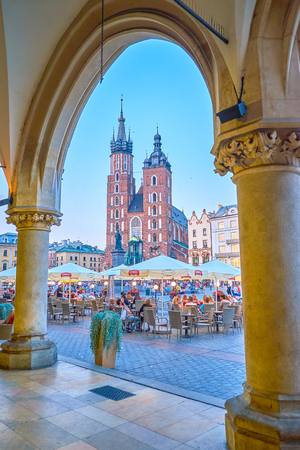 KRAKOW, POLAND - JUNE 11, 2018: The view on beautiful St Mary Basilica through the arcade of the Cloth Hall with summer terrace of restaurant in the middle, on June 11 in Krakow.