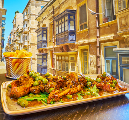 Enjoy the rabbit, stewed in red wine with beans, herbs and spices  in the popular restaurant of Strait street, Valletta, Malta. Фото со стока