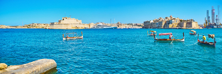 VALLETTA, MALTA - JUNE 17, 2018: The dghajsa and luzzu traditional Maltese boats at Quarry Wharf with a view on fortified cities of Birgu and Senglea, on June 17 in Valletta.
