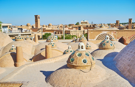 The walk among the brick domes on roof of Sultan Amir Ahmad (Qasemi Bathhouse) with a view on medieval windcatchers (badgirs) on the background, Kashan, Iran.