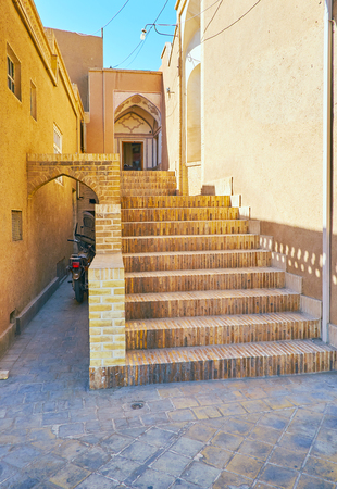 The narrow backstreet in old town with brick staircase, leading to the traditional Persian mansion, Kashan, Iran.
