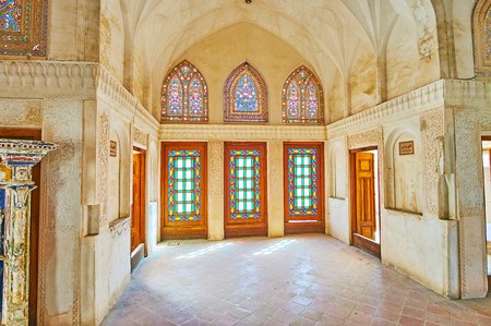 KASHAN, IRAN - OCTOBER 22, 2017: The fine floral patterns of stained-glass windows in Central Room (Shahneshin or Panjdari) of Abbasi House, on October 22 in Kashan.