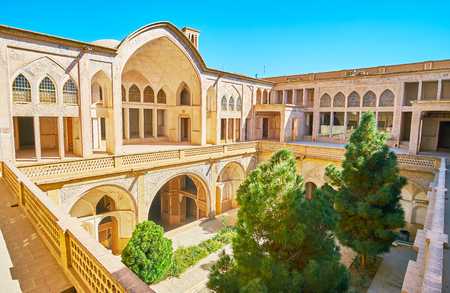 KASHAN, IRAN - OCTOBER 22, 2017: The Howz Khaneh courtyard of Abbasi House boasts the scenic iwan (portal) with carved stucco patterns, lush pine gardenon the ground floor and the pool, on October 22 in Kashan.