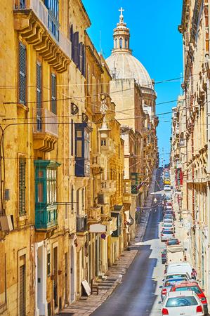 The huge stone dome of Carmelite (Our Lady of Mount Carmel) Church dominates the Old Mint street skyline, Valletta, Malta. Banco de Imagens