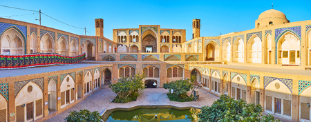 KASHAN, IRAN - OCTOBER 22, 2017: Panorama of the Agha Bozorg mosque with garden and madrasah on the ground floor, the beautiful portal and badgirs (wind towers) on the upper floor, on October 22 in Kashan.