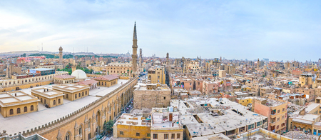 Panorama of Islamic Cairo with ramshackle houses, tall minarets and huge Al-Hussein Mosque on the foreground, Egypt