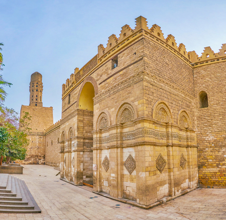 The Al-Hakim Mosque boasts surrounding defensive walls with huge Gatehouse and carved minarets on its perimeter, Cairo, Egypt Banco de Imagens