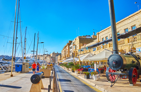 BIRGU, MALTA - JUNE 17, 2018: The pleasant walk along Vittoriosa marina with a view on vintage field kitchen and line of comfortable outdoor restaurant in Xatt Il-Forn promenade, on June 17 in Birgu. Редакционное