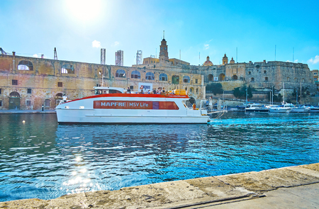 BIRGU, MALTA - JUNE 17, 2018: The modern ferry with tourists is arriving to the terminal of Birgu,  maneuvering in narrow Vittoriosa marina with a view on St Michael's bastion of Senglea (L-Isla) fortress, on June 17 in Birgu.