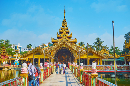 YANGON, MYANMAR - FEBRUARY 27, 2018:  The main shrine of Kyay Thone Pagoda (Bronze Buddha Image) with huge golden statue of Meditating Buddha, covered with pyatthat roof (multistaged), on February 27 in Yangon.